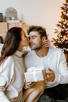 Giovani coppie che aprono i regali di natale nel loro salotto davanti all'albero di natale