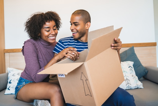 Giovani coppie che aprono un pacchetto a casa.