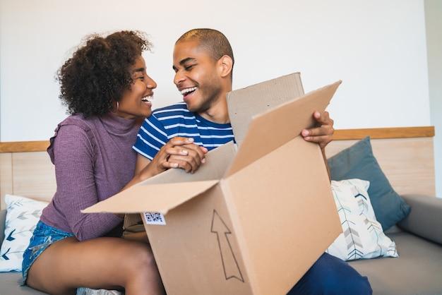 Giovani coppie che aprono un pacchetto a casa