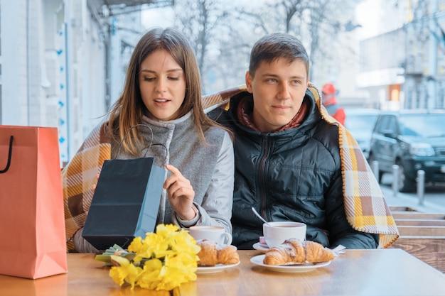 Giovani coppie in caffè all'aperto con i sacchetti della spesa