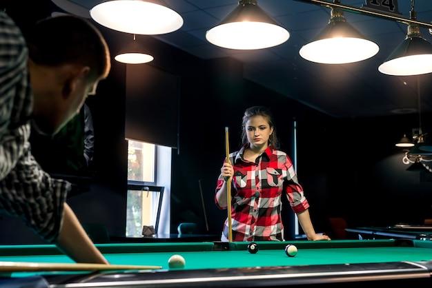 Coppia giovane giocando a biliardo, donna che si occupa del ragazzo