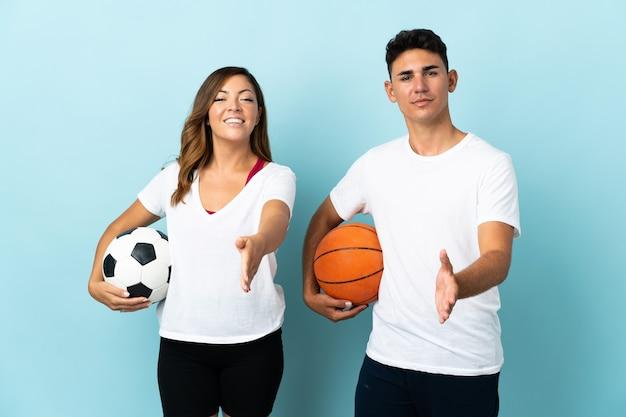 Giovani coppie che giocano a calcio e basket in blu che agitano le mani per la chiusura di un buon affare