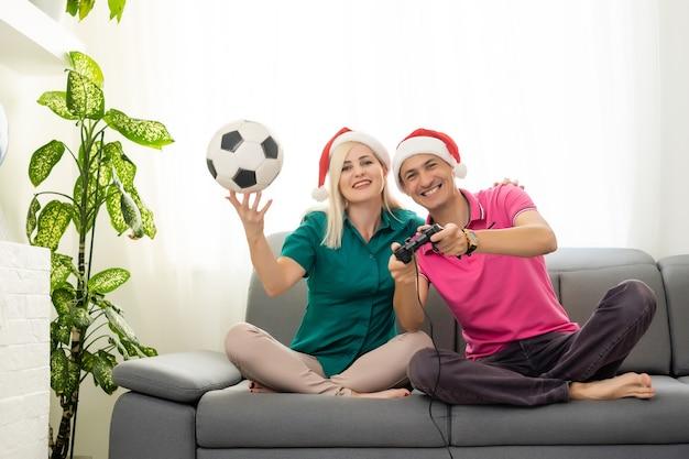 Giovane coppia che gioca al videogioco con i joystick a casa per natale