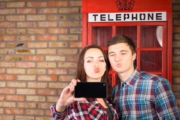 Coppia giovane in posa di fronte a una cabina telefonica britannica rossa iconica che si fa un selfie sul proprio telefono cellulare mentre tira facce stravaganti