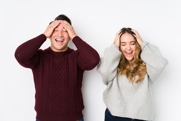 La giovane coppia in posa in un muro bianco ride con gioia tenendo le mani sulla testa. concetto di felicità.