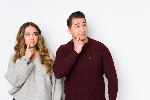 Giovani coppie che posano in una parete bianca che guarda lateralmente con l'espressione dubbiosa e scettica.
