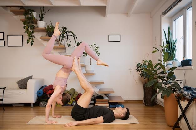 Giovani coppie che praticano acro yoga insieme a casa in un interno moderno. hobby, stare insieme, stile di vita sano