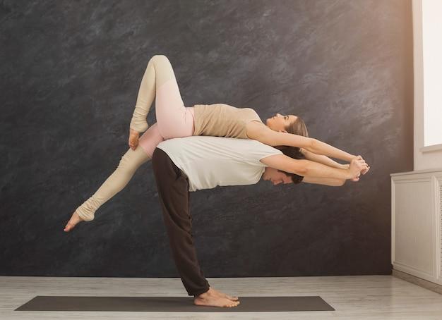 Giovani coppie che praticano insieme acroyoga sulla stuoia in palestra. uomo e donna che fanno esercizio di equilibrio e di allungamento della schiena, copia spazio, vista laterale. yoga del partner, concetto di flessibilità