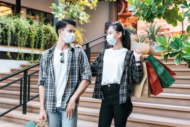 Giovane coppia in maschera di protezione che tiene più shopping bag di carta