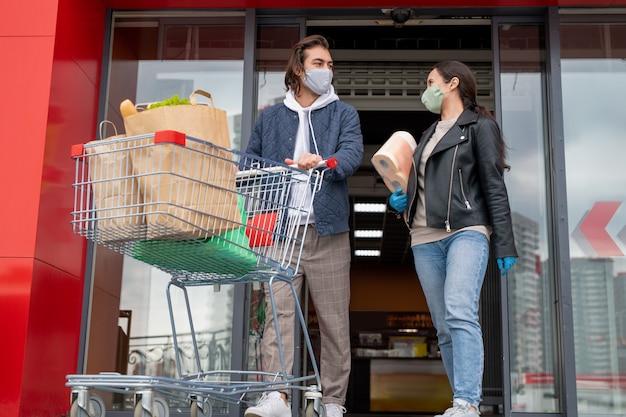 Coppia giovane in maschere protettive lasciando supermercato mentre l'uomo spinge il carrello