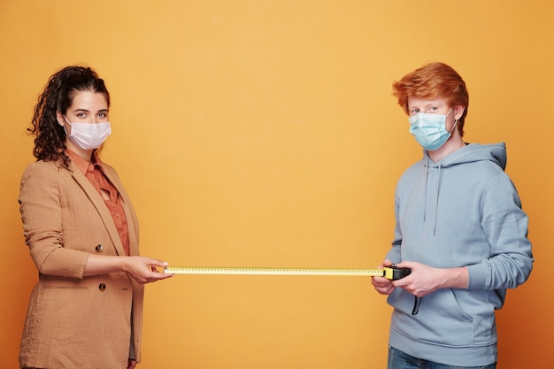 Coppia giovane in maschere protettive che misurano due metri tra di loro mentre in piedi contro il muro giallo davanti alla telecamera