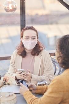 Giovane coppia in maschere protettive seduto al tavolo in caffè e parlare tra loro