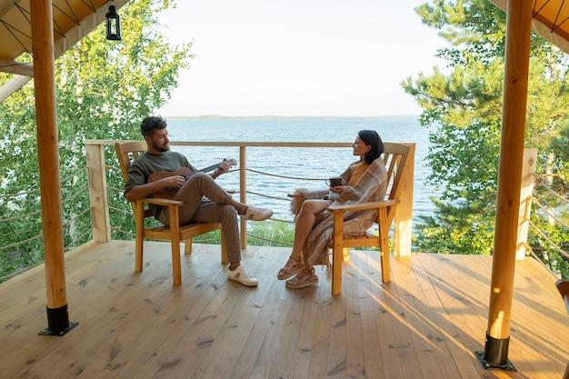 Giovane coppia che si rilassa nel patio della casa glamping