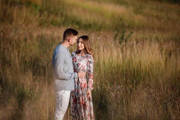 Giovani coppie che riposano in natura in un campo. coppia al tramonto