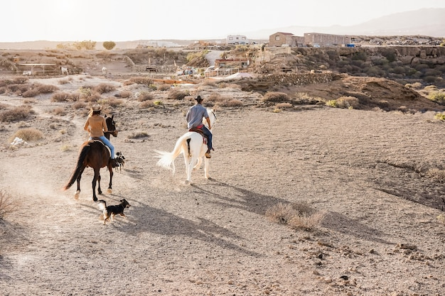 Giovane coppia a cavallo che fa un'escursione con animali domestici al tramonto - focus principale sulla schiena della donna Foto Premium