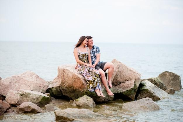 Giovane coppia sulle rocce nel mare
