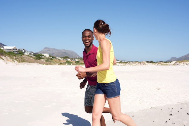 Giovani coppie che corrono insieme sulla spiaggia