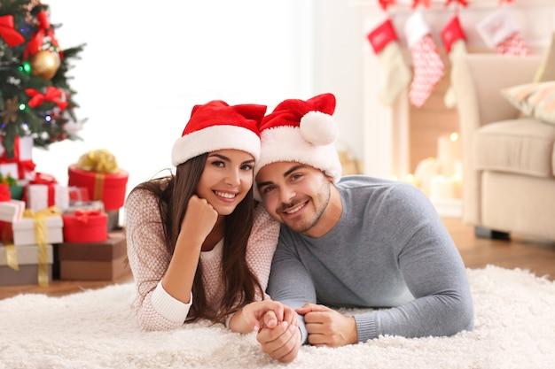 Giovane coppia in cappelli di babbo natale al chiuso