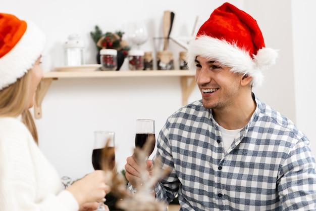 Giovane coppia in cappelli di babbo natale che beve vino e festeggia il natale