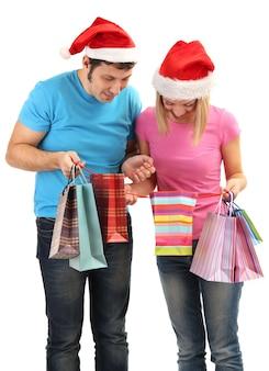 Giovane coppia in cappelli di babbo natale che fa shopping e tiene in mano molte borse della spesa isolate su bianco