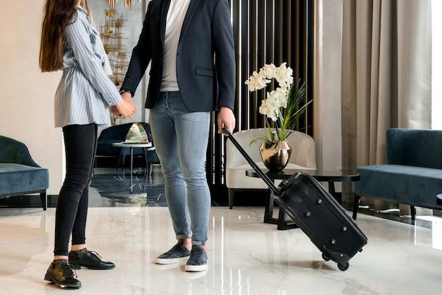 Giovani coppie che dicono addio in piedi nella hall dell'hotel prima che l'uomo se ne vada
