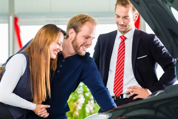 Giovani coppie e venditore con auto nel concessionario auto
