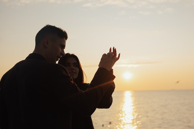 Giovani coppie che toccano sensualmente le mani al tramonto del mare. amore, romanticismo, tenerezza.