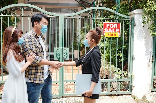 Giovane coppia che stringe la mano all'agente immobiliare dopo aver acquistato la prima casa