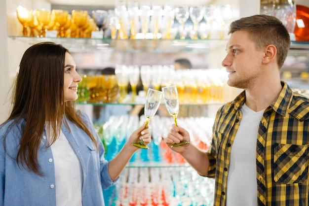 Coppia giovane allo scaffale con bicchieri di vino nel negozio di casalinghi. uomo e donna che acquistano beni per la casa nel mercato, famiglia nel negozio di articoli da cucina