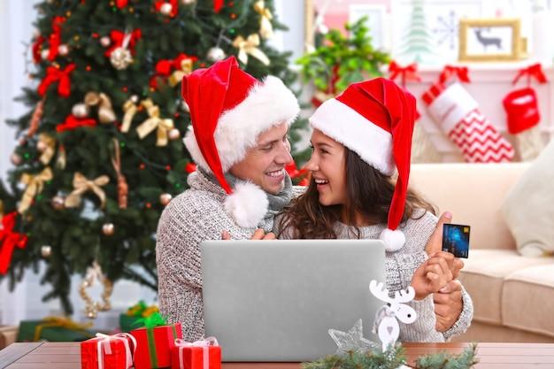 Giovane coppia che fa shopping online con carta di credito a casa per natale