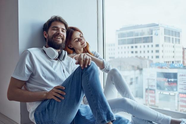 Una giovane coppia si siede vicino alla finestra con le cuffie insieme appartamenti