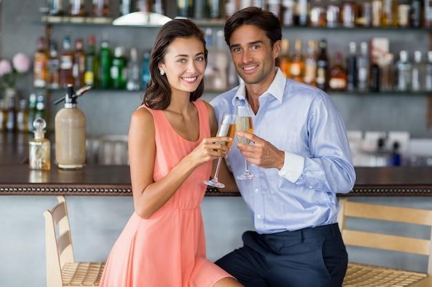 Coppia giovane seduto al bancone del bar e brindando con un bicchiere di champagne