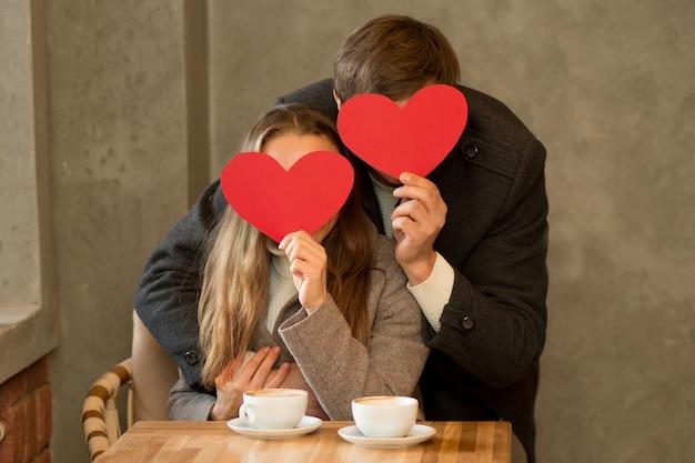 Coppia giovane seduto in caffe con caffè, bouquet di rose, tenendo il cuore di carta vicino a facce. giorno di san valentino. foto di alta qualità