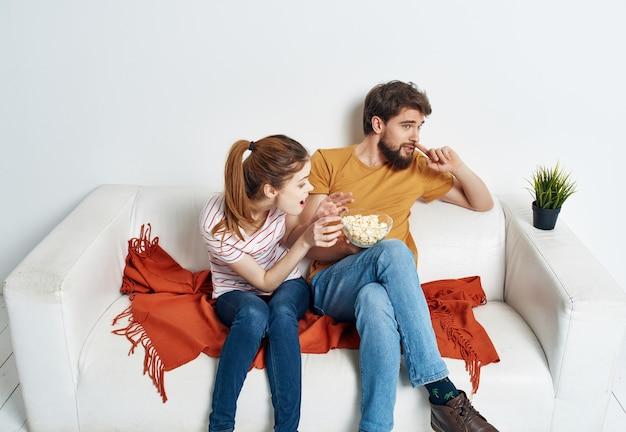 Giovane coppia seduta sul divano popcorn a guardare un film in vacanza in famiglia