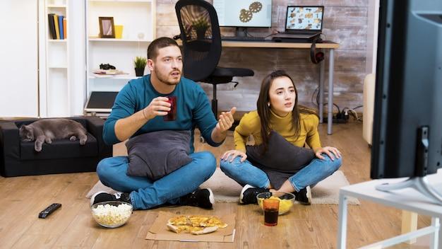 Giovane coppia seduta sul pavimento che rallegra, mangia cibo spazzatura mentre guarda il campionato sportivo in tv e il gatto dorme.