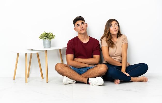 Giovane coppia seduta sul pavimento su bianco e alzando lo sguardo