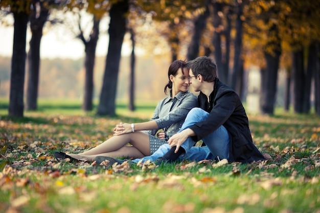 Coppia giovane seduto per terra nel parco in autunno