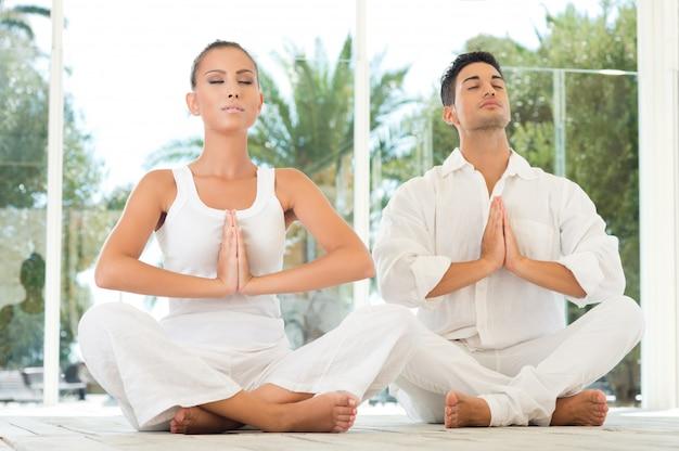 Giovane coppia seduta in una posa di loto e meditando durante l'allenamento allo yoga