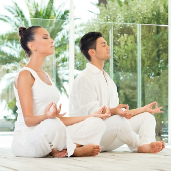 Giovane coppia seduta in una posa di loto e meditando
