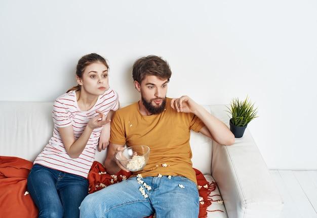 Coppia giovane seduto accanto a popcorn a guardare la tv rest