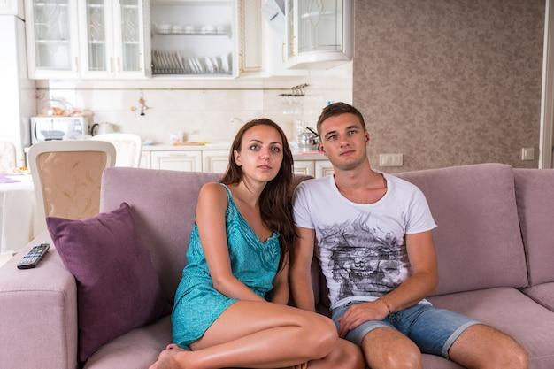 Giovane coppia seduta fianco a fianco sul divano viola e guardare la televisione con espressioni vuote durante una giornata di relax a casa