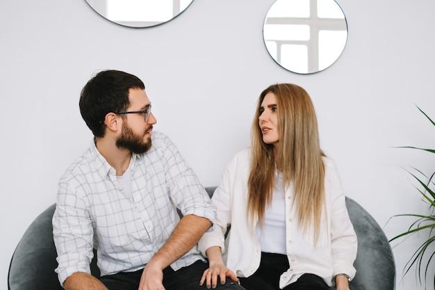 Giovani coppie che si siedono sul divano a casa e parlano tra loro.