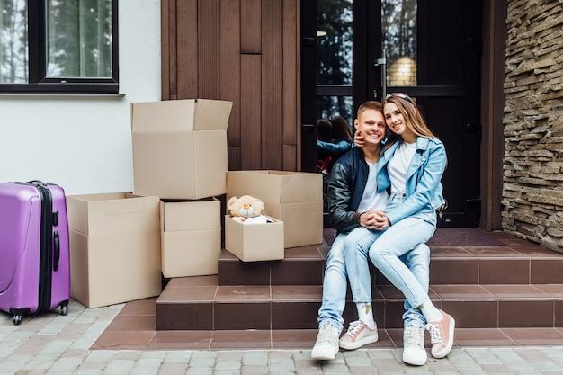 Giovani coppie che si siedono sulle scale divertendosi le scatole di imballaggio il giorno commovente, ragazzo amoroso che fa a regalo un orsacchiotto.