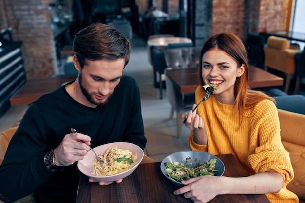 Giovani coppie che si siedono al tavolo che mangiano comunicazione di stile di vita sano