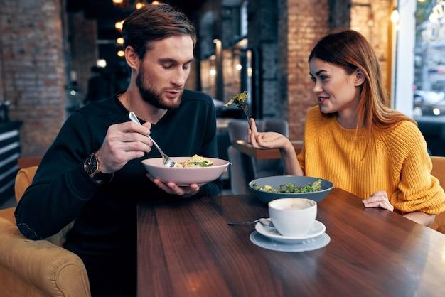Giovani coppie che si siedono alla tavola che mangiano comunicazione di stile di vita sano