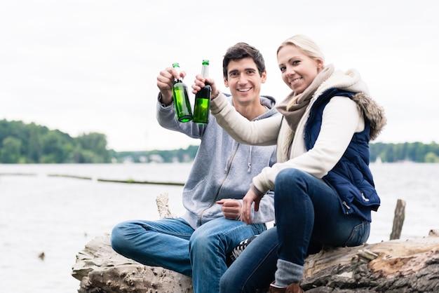 Giovani coppie che si siedono sul ceppo di albero in riva al fiume a bere birra e dire applausi