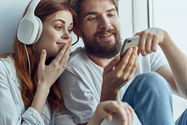 Una giovane coppia seduta sul davanzale della finestra romanticismo gioia tecnologia