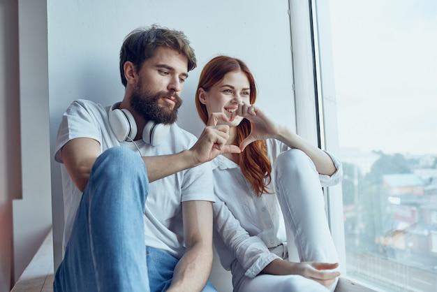 Una giovane coppia seduta sul davanzale della finestra gioia romantica
