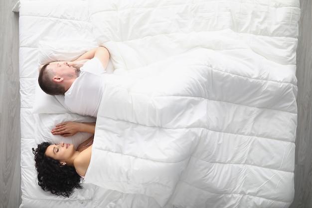 Giovane coppia che dorme pacificamente su un letto grande e comodo