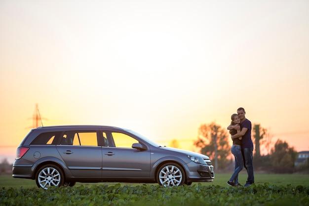 Giovane coppia, donna magra e attraente con una lunga coda di cavallo e un bell'uomo in piedi all'auto d'argento?